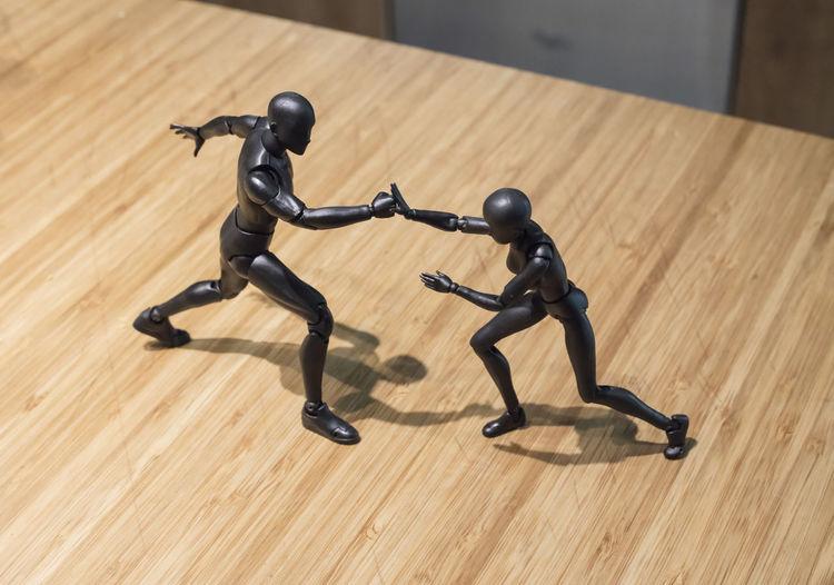 Two fighting figures. Martial arts postures. Fight Block Blocking  Close-up Fighting Figures Hardwood Floor Indoors  Two Figures Fighting