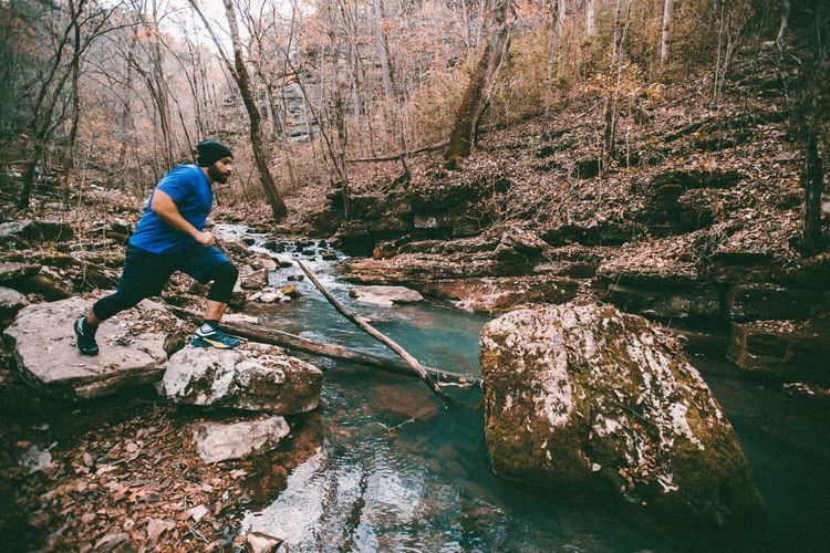Man Running On Rocks At Forest