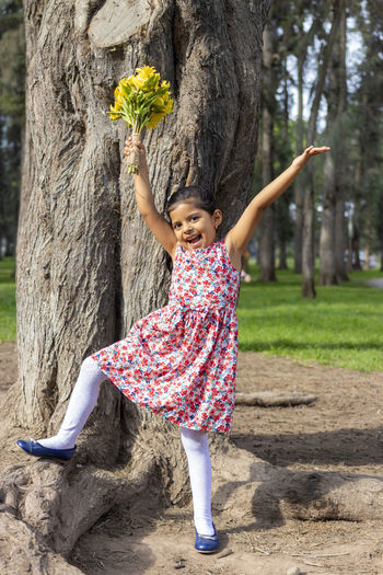 Full length portrait of cute girl standing by tree