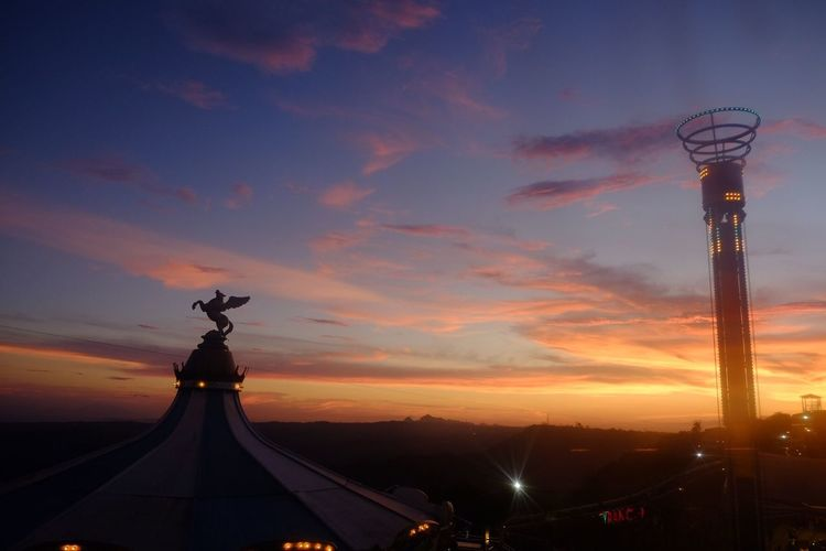 Statue of illuminated city at sunset