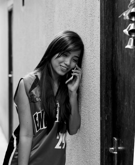 Young Woman Talking On Phone By Wall