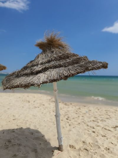 Thatched roof on beach against sky