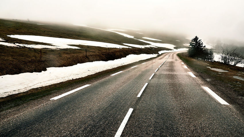 The Road Beauty In Nature Cold Temperature Focus On Foreground Foggy Landscape Mountain Nature No People Outdoors Road Scenics Snow Wet Wet Ground Winter