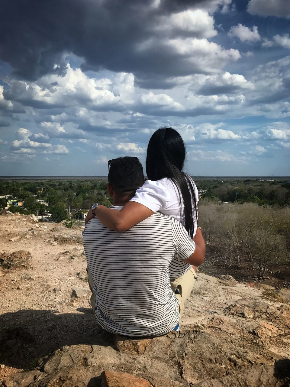 Rear View Of Couple Sitting On Rock Against Landscape