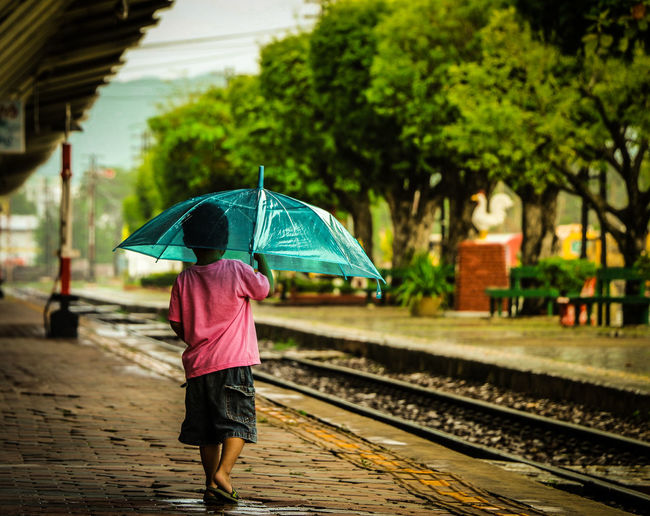 Rear View Of Boy With Umbrella Walking On Railroad Station