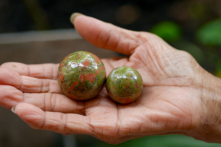 Close-up of hand holding sphere shape objects