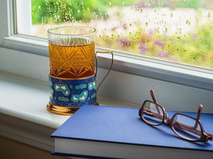 Close-up of glasses on window sill