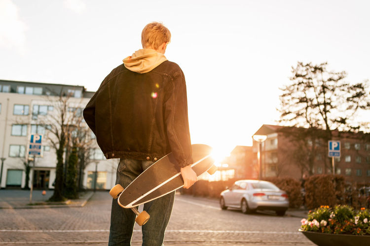 Man standing on street in city against sky