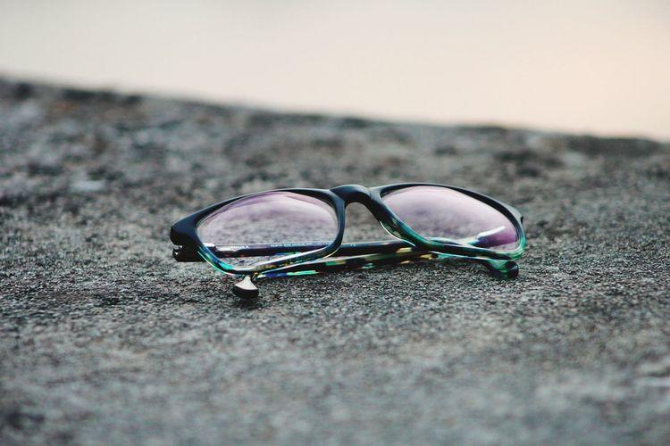 Close-up of sunglasses on sand