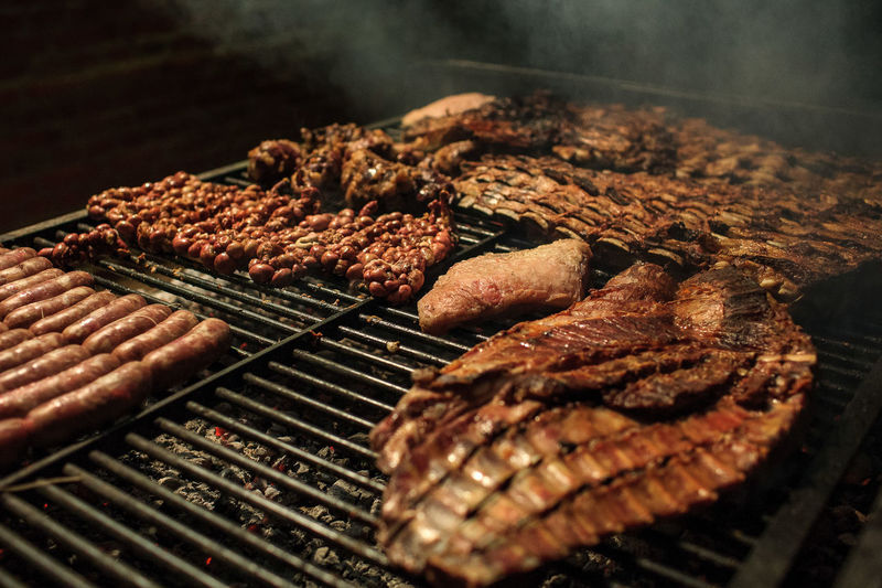 Close-up of meat on barbecue grill at night
