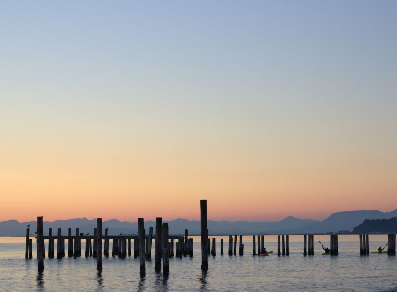 Wooden Posts On River Against Clear Sky During Sunset
