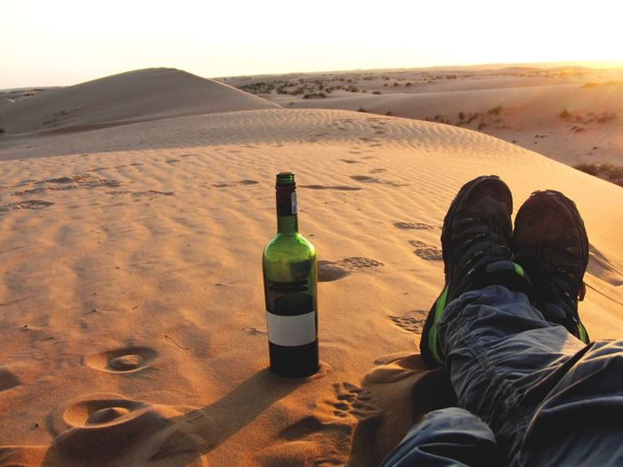 Low section of man sitting by wine bottle on sand at desert