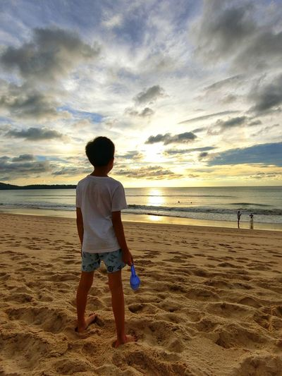 Rear view of boy standing on beach against sky