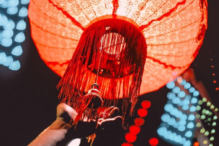 Cropped hand touching illuminated lantern