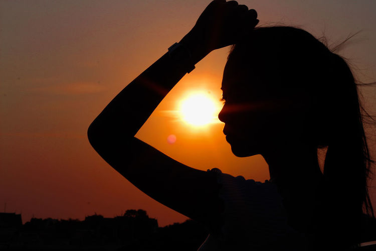 Silhouette woman standing against sun during sunset