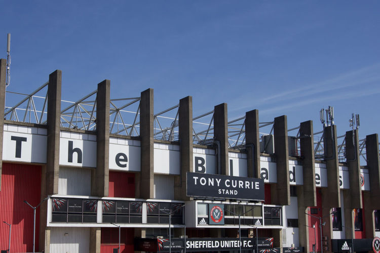 Exterior view of Tony Currie Stand at Bramall Lane Football Ground, Sheffield United.on a sunny day with blue sky and copy space Sheffield Sheffield United Bramall Lane Football Stadium Ground Standing Yorkshire Blades Text Western Script Sky Architecture Building Exterior Built Structure Information Sign City No People Day Information Sign Copy Space Outdoors Script Clear Sky Capital Letter