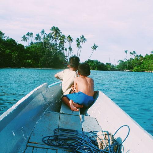 Man sitting in boat on sea against sky