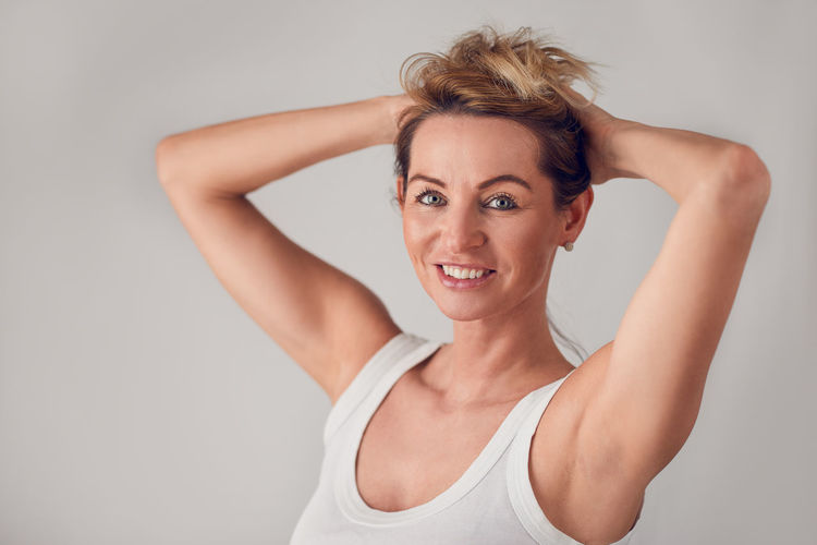 Attractive blond woman holding up her long hair Beautiful Copy Space Hair Happiness Happy Looking At Camera Woman Attractive Beautiful People Beauty Best Ager Blond Cheerful Face Gray Background Happiness Holding Hair Up Looking At Camera Middle-aged One Woman Only Portrait Real People Studio Shot