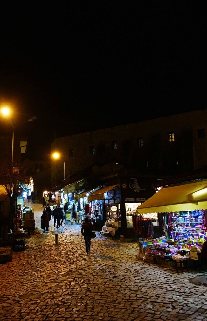 night, illuminated, street, market, retail, city, real people, market stall, lighting equipment, group of people, building exterior, architecture, for sale, built structure, street market, small business, incidental people, lifestyles, business, street light, outdoors