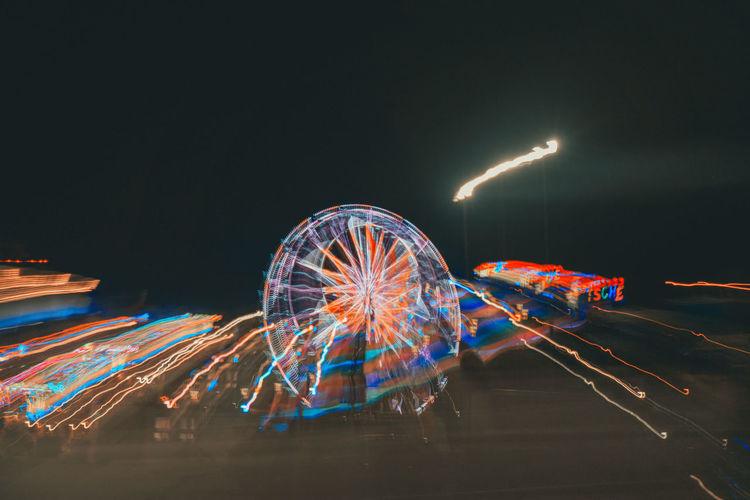 Illuminated ferris wheel against sky at night