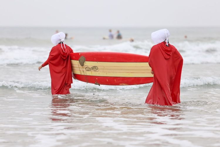 """Blackies Halloween Surf Contest Series • """"The bath is required before the Ceremony. I am to make myself clean. Washed and brushed like a prized pig."""" -Handmaid's Tale Red Sea Water Beach Rear View Nature Carrying Beauty In Nature Scenics Women Day Outdoors Standing Horizon Over Water Lifestyles Wave Full Length Halloween Costumes Surfboard Surfing Surfers Handmaid's Tale Costume Halloween 2017 Halloween_Collection"""