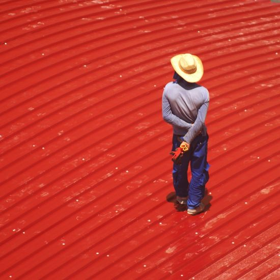 Manual worker walking on red surface