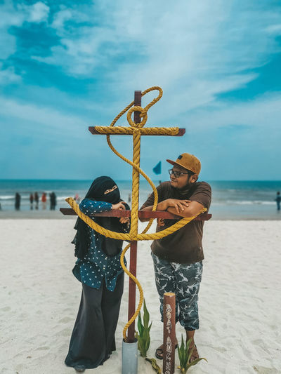 Man and woman standing at beach against sky