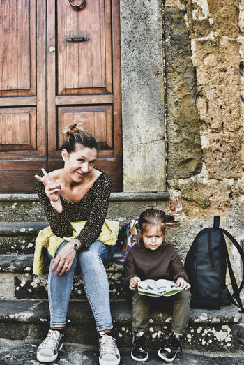 Portrait of smiling mother with daughter sitting on steps