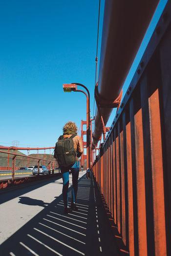 Rear view of woman walking on bridge against clear blue sky