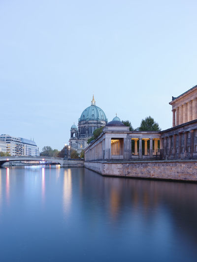 Illuminated bridge by berlin cathedral over river during sunset