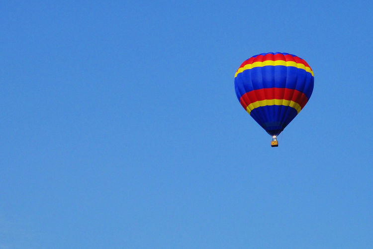 Adventure Air Vehicle Balloon Ballooning Festival Blue Clear Sky Copy Space Day Exhilaration Extreme Sports Flying Freedom Hot Air Balloon Low Angle View Mid-air Multi Colored Nature Outdoors Parachute Sky Sport Transportation End Plastic Pollution