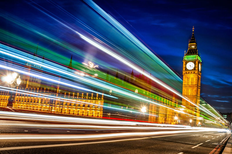 Light trail on westminster bridge with illuminated big ben against sky