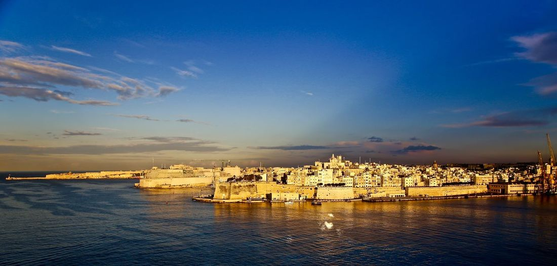Setting sun over Valletta Harbour Architecture Blue Cloud - Sky Distant Dusk Light No People Outdoors Sea Sky