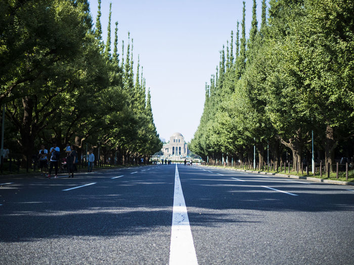 Road amidst trees in city against clear sky