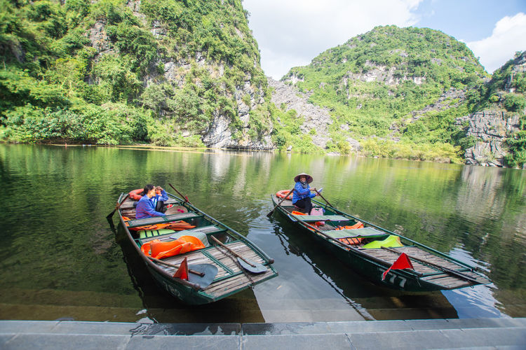 tourist sitting on boat at Trang An, Ninh Binh, Vietnam. Nautical Vessel Transportation Mode Of Transportation Water Plant Real People Tree Nature Men Day River Beauty In Nature Scenics - Nature Waterfront People Lifestyles Leisure Activity Non-urban Scene Outdoors
