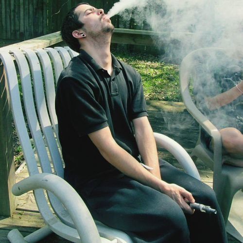 Young Man Smoking Shisha While Sitting On Chair In Yard