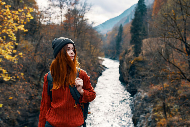 Smiling young woman standing by tree during autumn
