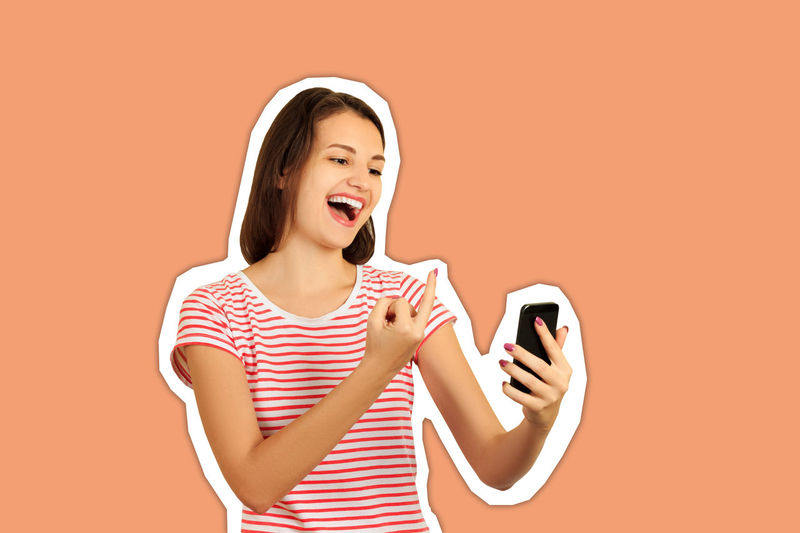 Smiling young woman using smart phone against orange background