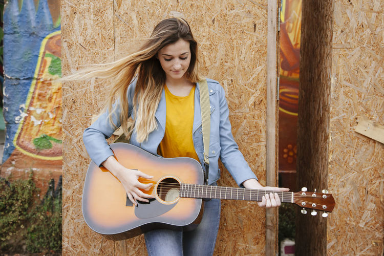 Woman playing guitar while standing by wall