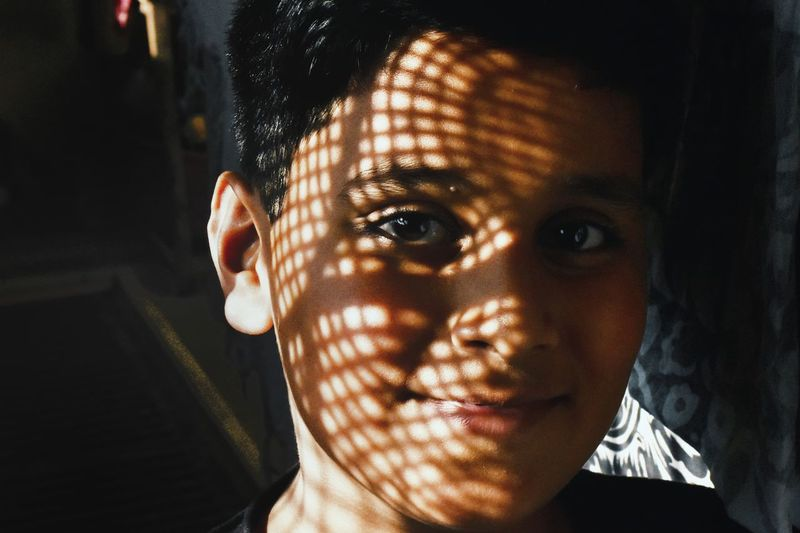 Close-up portrait of smiling teenage boy with sunlight and shadow on face at home