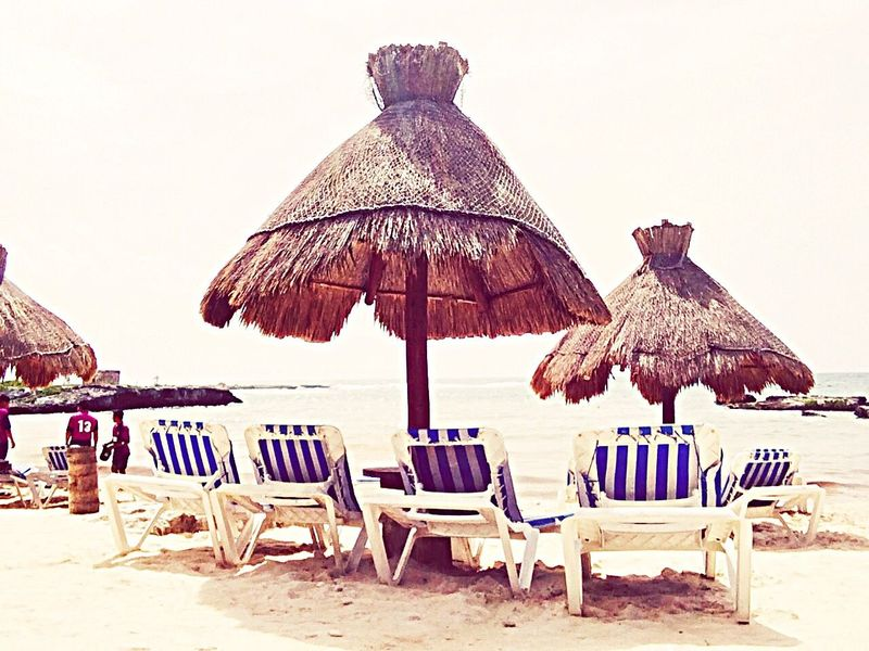 Beach Parasol Sand Thatched Roof Shore Beach Umbrella Chair Protection Absence Umbrella Sunshade Empty Clear Sky Horizon Over Water Incidental People Lounge Chair Sea Group Of Objects Vacations Tranquility
