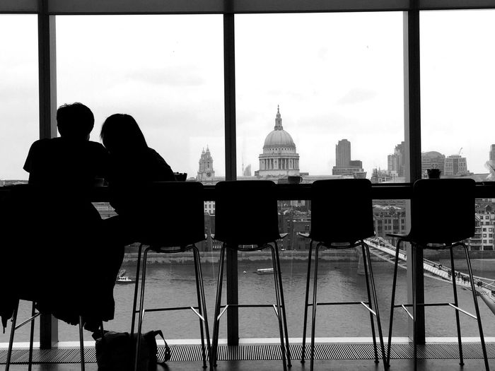 Rear View Of Man And Woman Sitting In Restaurant In Front Of St Pauls Cathedral