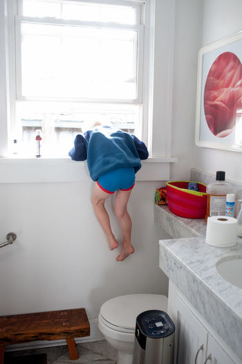 Rear view of boy climbing on window in bathroom at home