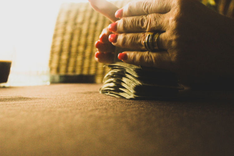 Cropped hands of woman shuffling cards on table