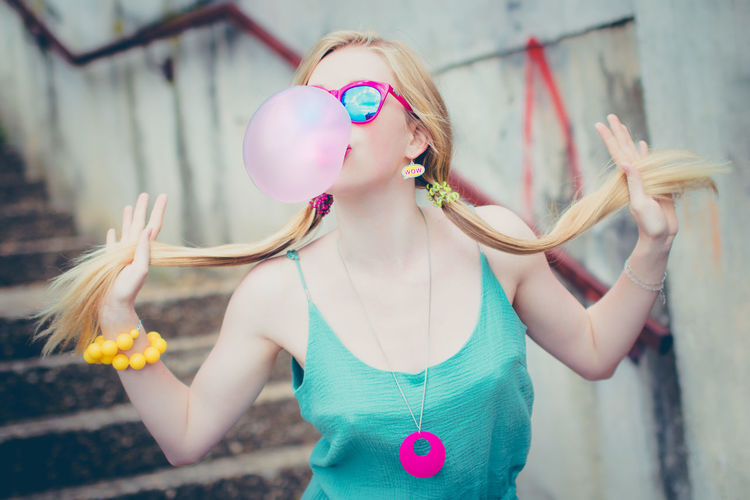 Fashionable young woman holding ponytails while blowing bubble gum