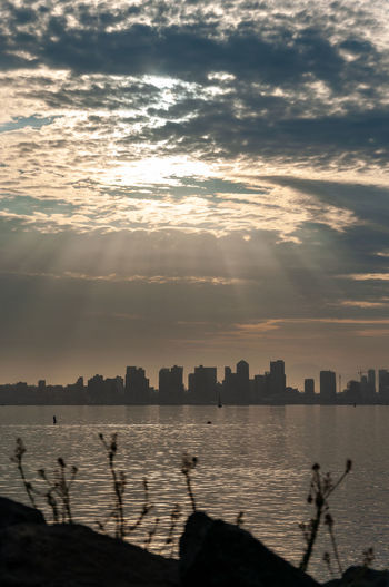 Silhouette buildings by lake against cloudy sky during sunset