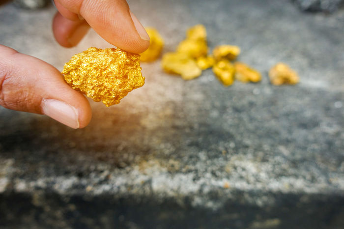 Gold ore on hand Gold Beauty In Nature Close-up Day Food Food And Drink Freshness Gold Ore Healthy Eating Holding Human Body Part Human Finger Human Hand Investment Lifestyles Money Nature One Person Outdoors People Ready-to-eat Real People Yellow