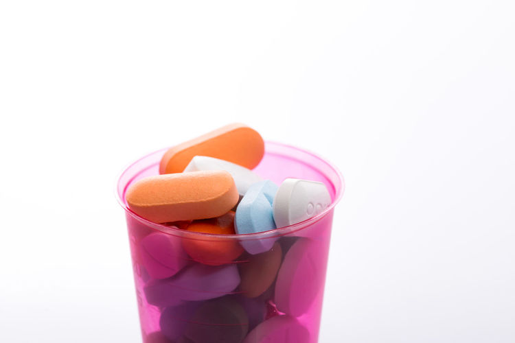 Close-up of medicines in container against white background