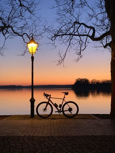 Bicycle on street by lake against sky during sunset