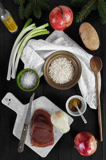 Ingredients for the risotto recipe with scamorza cheese and smoked tuna fish. Photographed from above, on a black wooden background. Ingredients Rice Bowl Coarse Salt Cooking From Scratch Cutting Board Directly Above Food Food And Drink Healthy Eating Healthy Eating Close-up Freshness High Angle View Ingredient Kitchen Utensil Olive Oil Pomegranate Preparation  Preparing Food Raw Potato Risotto Ingredients Smoked Cheese Smoked Tuna Fish Spoon Table Vegetable